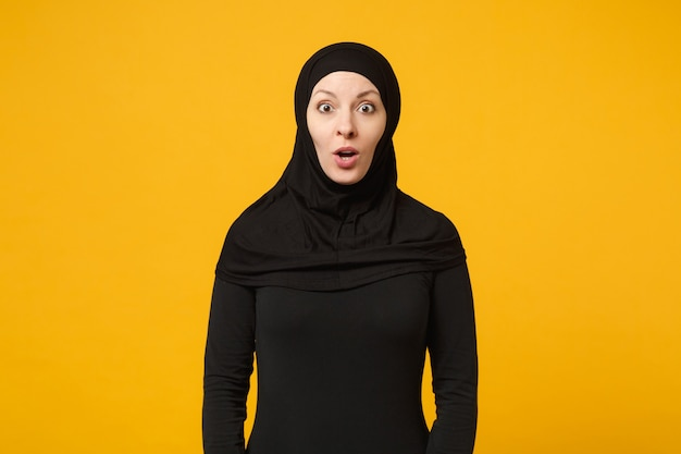 Zaskoczony piękna młoda arabska muzułmańska kobieta w czarnym hidżabie, dorywczo ubraniach na białym tle na portret żółtej ściany. koncepcja życia religijnego ludzi.