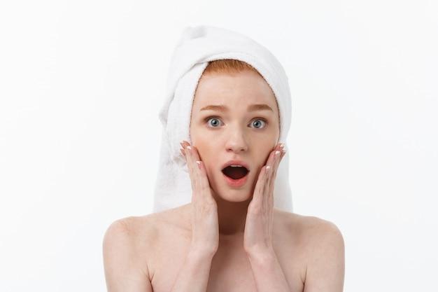 Zaskoczony, piękna, młoda kobieta po kąpieli z ręcznikiem na głowie na białym tle. motyw do pielęgnacji skóry i spa.