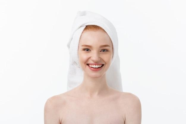 Zaskoczony, piękna, młoda kobieta po kąpieli z ręcznikiem na głowie na białym tle.