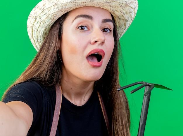 Zaskoczony piękny ogrodnik dziewczyna w mundurze na sobie kapelusz ogrodniczy trzymając grabie motyka i trzymając aparat na białym tle na zielono