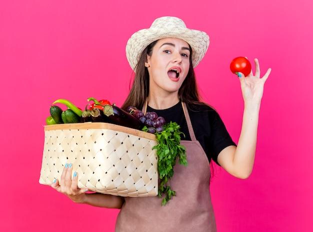 Zaskoczony piękny ogrodnik dziewczyna w mundurze na sobie kapelusz ogrodniczy trzymając kosz warzyw z pomidorem na białym tle na różowym tle