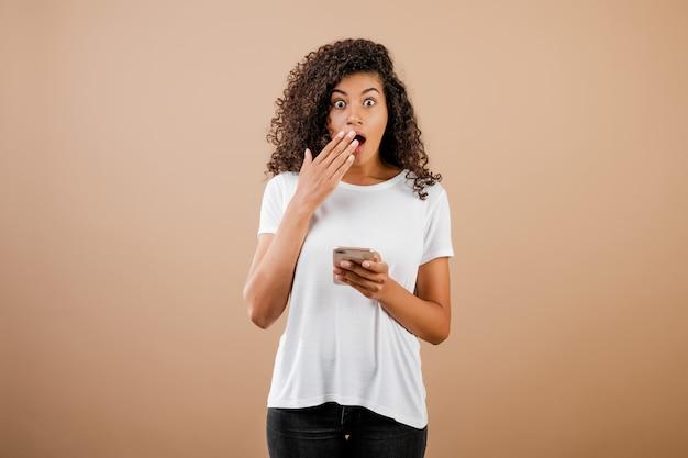 Zaskoczony podekscytowany młoda czarna dziewczyna z telefonem w ręku na białym tle nad brązowy