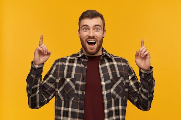 Zaskoczony, podekscytowany młody brodaty mężczyzna w kraciastej koszuli z otwartymi ustami, krzyczy i wskazuje w niebo obiema rękami nad żółtą ścianą