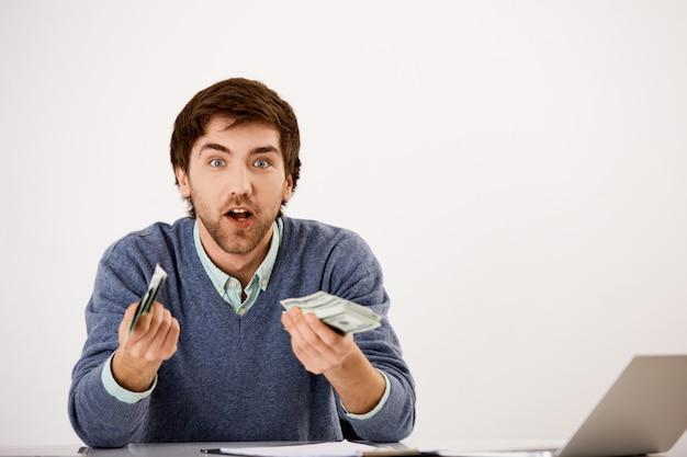 Zaskoczony, podekscytowany młody człowiek zarobił tysiące dolarów, zrobił wiele, trzymał gotówkę i gapił się pod wrażeniem