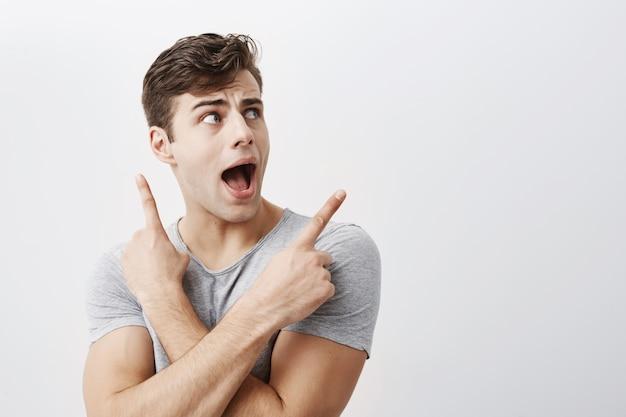 Zaskoczony, podekscytowany pozytywnie młody mężczyzna z ciemnymi włosami, wskazuje na miejsce z palcami wskazującymi coś reklamuje, szeroko otwiera usta. ludzie, reklama, koncepcja niespodzianki
