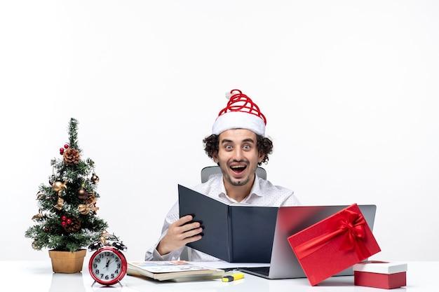 Zaskoczony podekscytowany pozytywny młody biznesmen z zabawnym czapką świętego mikołaja sprawdzanie informacji w dokumentach w biurze na białym tle