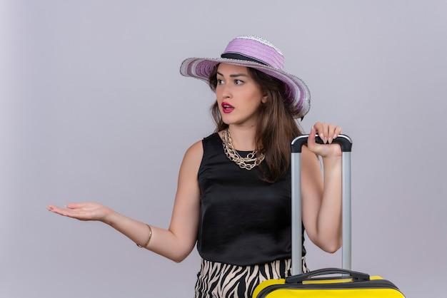 Zaskoczony podróżnik młoda dziewczyna ubrana w czarny podkoszulek w kapeluszu wyciągnął rękę w bok na białym tle