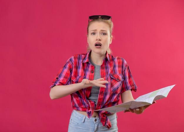 Zaskoczony podróżnik młoda dziewczyna ubrana w czerwoną koszulę i okulary na głowie trzymając mapę na na białym tle różowym