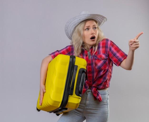 Zaskoczony podróżnik młoda dziewczyna ubrana w czerwoną koszulę w kapeluszu trzymając walizkę wskazuje na bok na na białym tle
