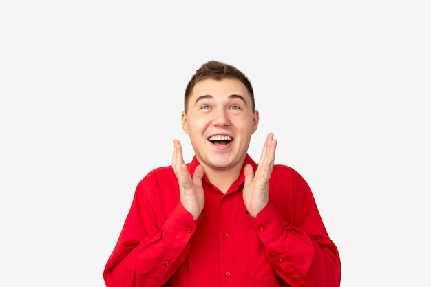 Zaskoczony portret mężczyzny. sukces promocji. zdumiony facet w czerwonej koszuli na białym tle.