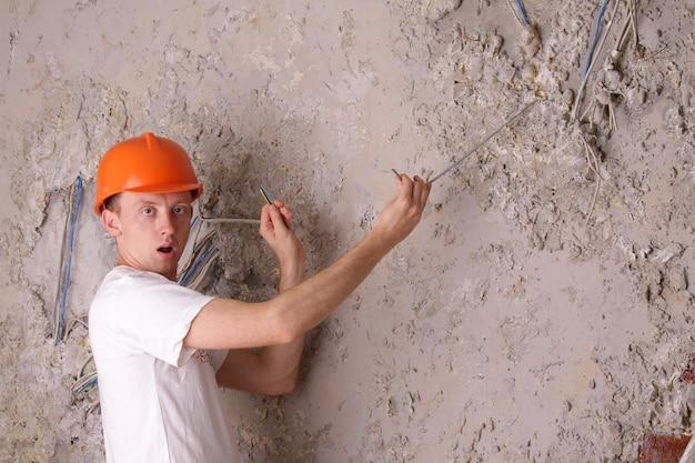 Zaskoczony pracownik elektryczny próbuje naprawić zepsute przewody
