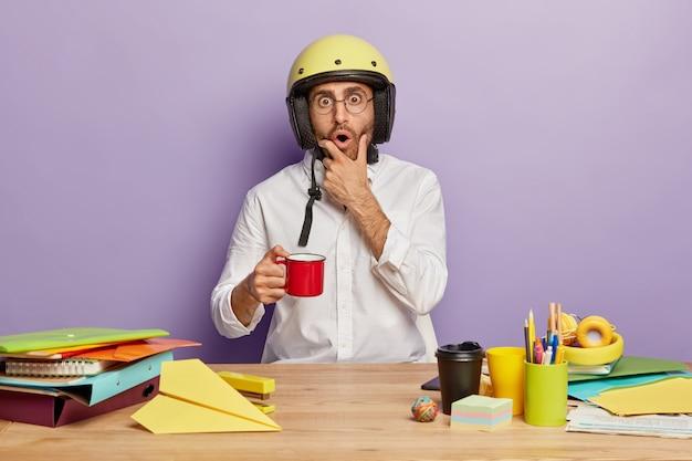 Zaskoczony pracownik siedzący przy biurku