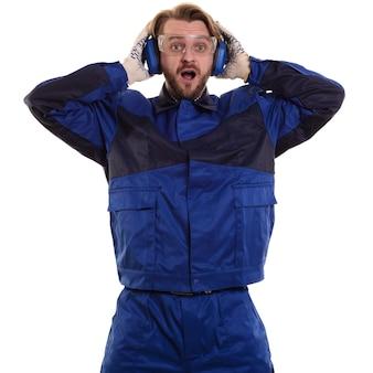 Zaskoczony pracownik w okularach stoi z ustami i trzyma słuchawki ochronne