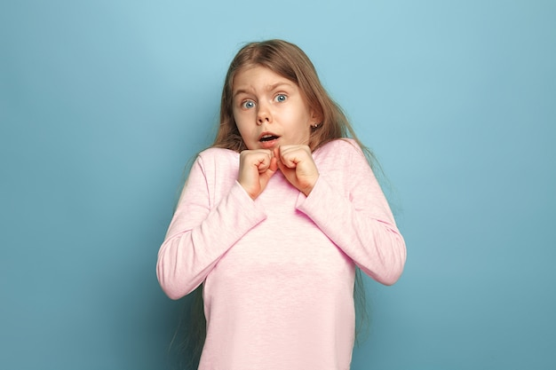 Zaskoczony przestraszona dziewczyna nastolatka na niebieskim tle studia. wyraz twarzy i koncepcja emocji ludzi.