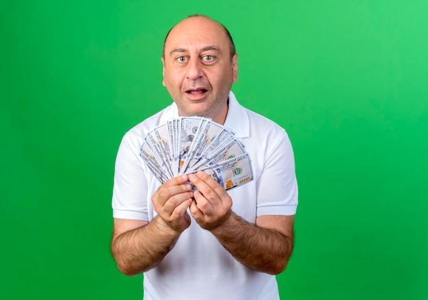Zaskoczony przypadkowy dojrzały mężczyzna trzyma gotówkę na białym tle na zielonej ścianie