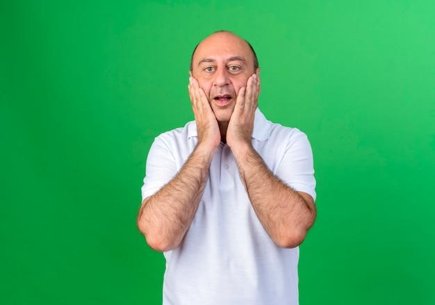 Zaskoczony przypadkowy dojrzały mężczyzna zakrył twarz rękami odizolowanymi na zielonej ścianie