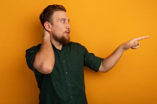 Zaskoczony przystojny blondyn kładzie rękę na głowie za patrząc i wskazując na bok na białym tle na pomarańczowej ścianie