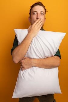 Zaskoczony przystojny blondyn kładzie rękę na ustach i trzyma poduszkę na pomarańczowo