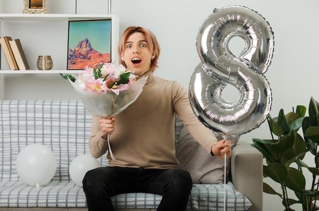 Zaskoczony przystojny facet w szczęśliwy dzień kobiet trzymający balon numer osiem i bukiet, siedzący na kanapie w salonie