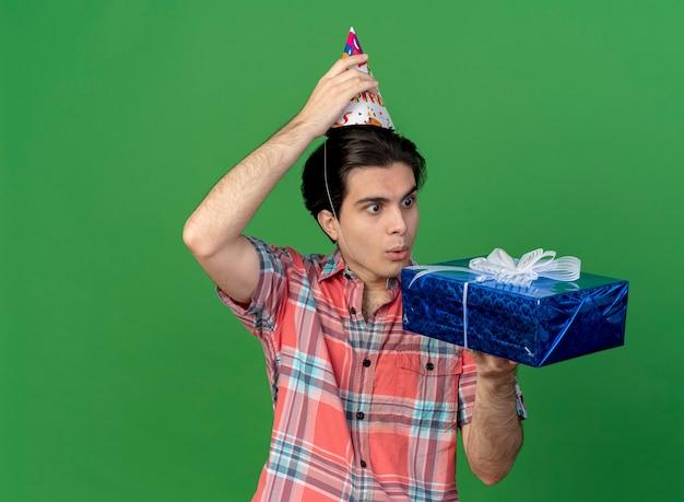 Zaskoczony przystojny kaukaski mężczyzna noszący i trzymający urodzinową czapkę patrzący na pudełko prezentowe