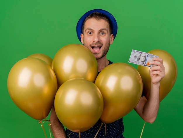 Zaskoczony przystojny kaukaski mężczyzna ubrany w niebieski kapelusz partii trzyma balony z helem i pieniądze na białym tle na zielonym tle z miejsca na kopię