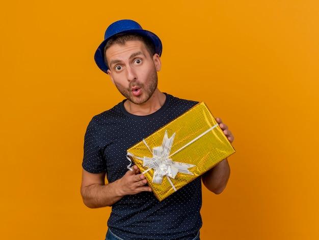 Zaskoczony przystojny kaukaski mężczyzna ubrany w niebieski kapelusz partii trzyma pudełko na białym tle na pomarańczowym tle z miejsca na kopię