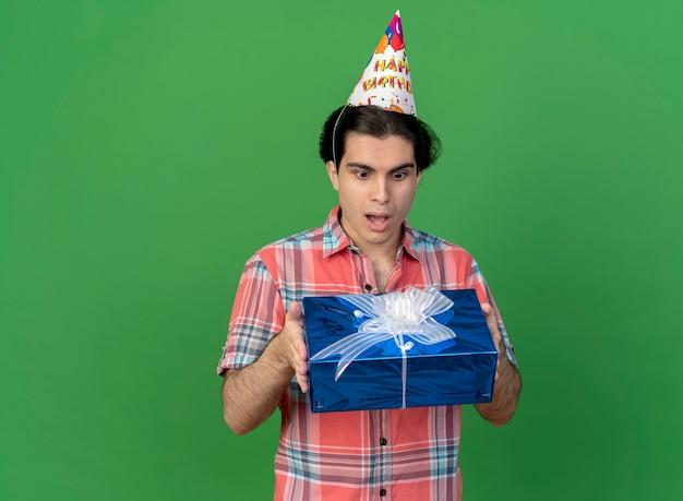 Zaskoczony przystojny kaukaski mężczyzna w czapce urodzinowej trzyma i patrzy na pudełko prezentowe gift