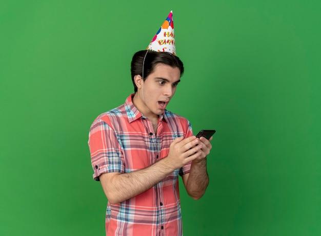 Zaskoczony przystojny kaukaski mężczyzna w czapce urodzinowej trzyma i patrzy na telefon