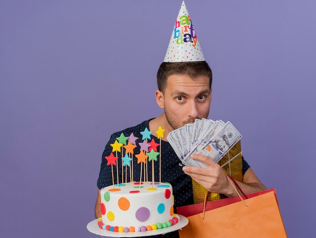 Zaskoczony przystojny kaukaski mężczyzna w czapce urodzinowej trzyma papierową torbę na zakupy z torbą na urodziny i pieniądze na fioletowym tle z miejsca na kopię