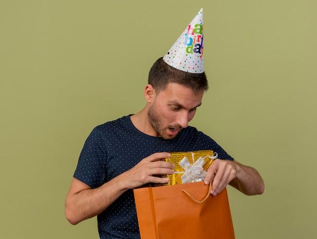Zaskoczony przystojny kaukaski mężczyzna w czapce urodzinowej trzyma pudełko w papierowej torbie na zakupy i patrzy na pudełko na białym tle na oliwkowym tle z miejsca na kopię