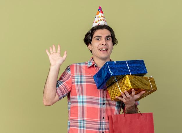 Zaskoczony przystojny kaukaski mężczyzna w czapce urodzinowej z podniesioną ręką trzyma pudełka na prezenty i papierową torbę na zakupy