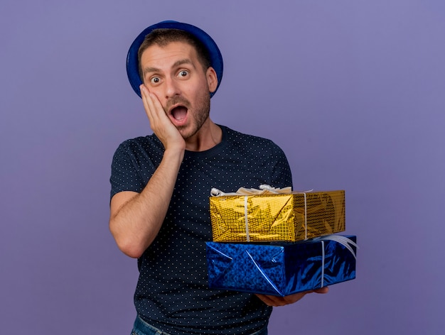 Zaskoczony przystojny kaukaski mężczyzna w niebieskim kapeluszu kładzie rękę na twarzy i trzyma pudełka na prezent na fioletowym tle z miejsca na kopię