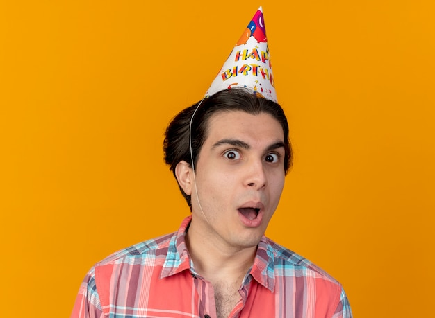 Zaskoczony przystojny kaukaski mężczyzna w urodzinowej czapce patrzy na kamerę looks