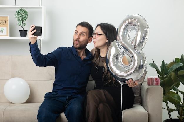 Zaskoczony, przystojny mężczyzna robi selfie z ładną młodą kobietą w okularach optycznych trzymając balon w kształcie ósemki i siedzi na kanapie w salonie w marcowy międzynarodowy dzień kobiet