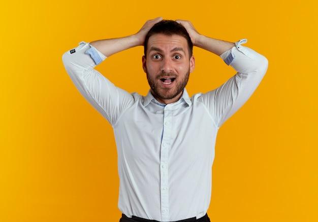 Zaskoczony przystojny mężczyzna trzyma głowę patrząc na białym tle na pomarańczowej ścianie