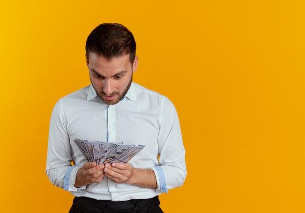 Zaskoczony przystojny mężczyzna trzyma i patrzy na pieniądze na białym tle na pomarańczowej ścianie