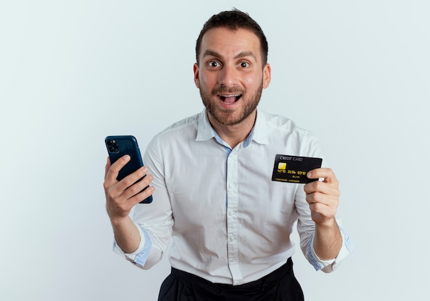 Zaskoczony przystojny mężczyzna trzyma kartę kredytową i telefon na białym tle na białej ścianie