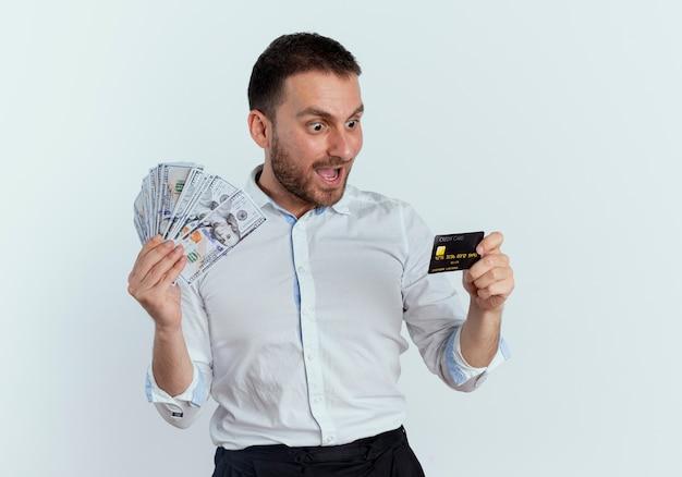 Zaskoczony przystojny mężczyzna trzyma pieniądze i patrzy na kartę kredytową na białej ścianie