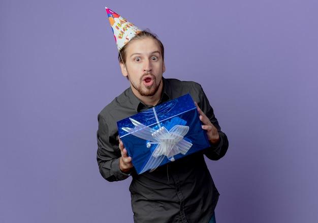 Zaskoczony przystojny mężczyzna w czapce urodzinowej trzyma pudełko na białym tle na fioletowej ścianie