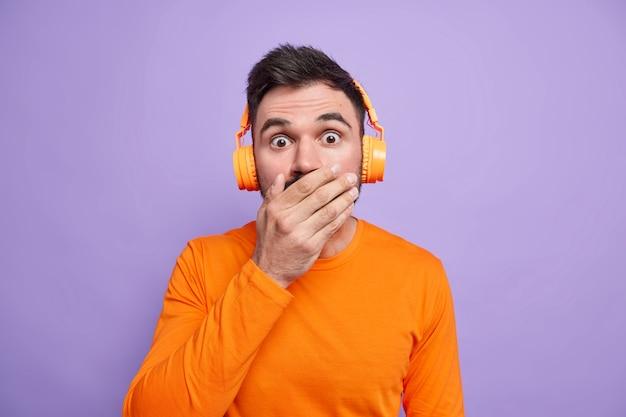 Zaskoczony przystojny mężczyzna zakrywa usta i wygląda na oszołomionego, będąc zszokowany czymś strasznym, ma na sobie jasnopomarańczowy sweter i słucha ścieżki dźwiękowej przez bezprzewodowe słuchawki
