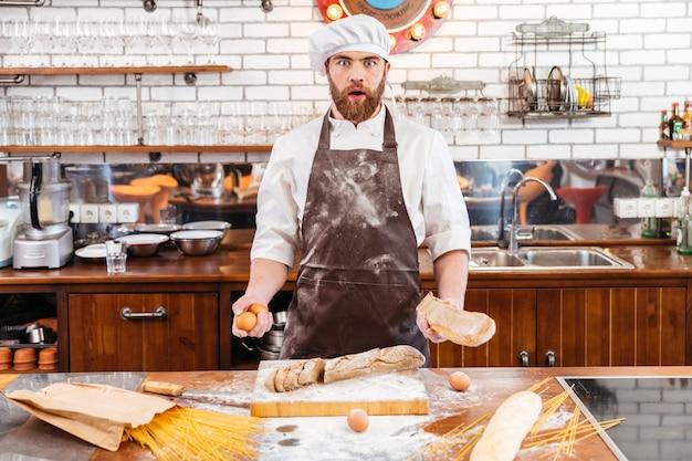 Zaskoczony przystojny piekarz krojący chleb i trzymający jajka w kuchni