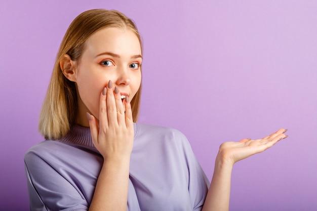 Zaskoczony radosny podekscytowany blondynka kaukaski całkiem młoda kobieta obejmuje usta ręką. nastoletnia dziewczyna pokazuje gest po stronie ręcznie na miejsce na miejsce na na białym tle kolor fioletowy.