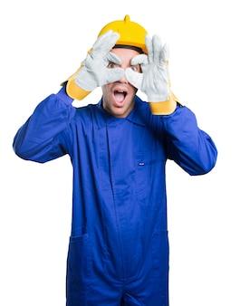 Zaskoczony robotnik, używając dłoni jak lornetki na białym tle