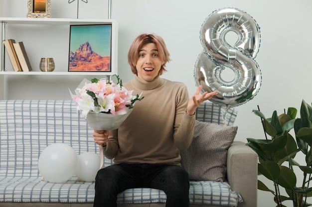 Zaskoczony rozkładający rękę przystojny facet na szczęśliwy dzień kobiet trzymający bukiet siedzący na kanapie w salonie