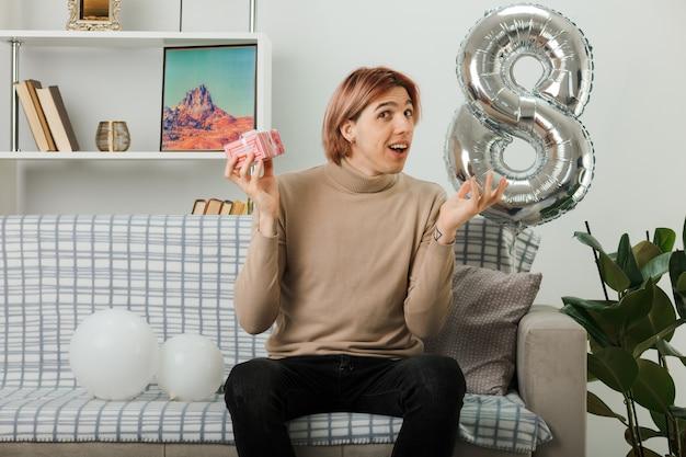 Zaskoczony rozkładający rękę przystojny facet na szczęśliwy dzień kobiet trzymający prezent siedzący na kanapie w salonie