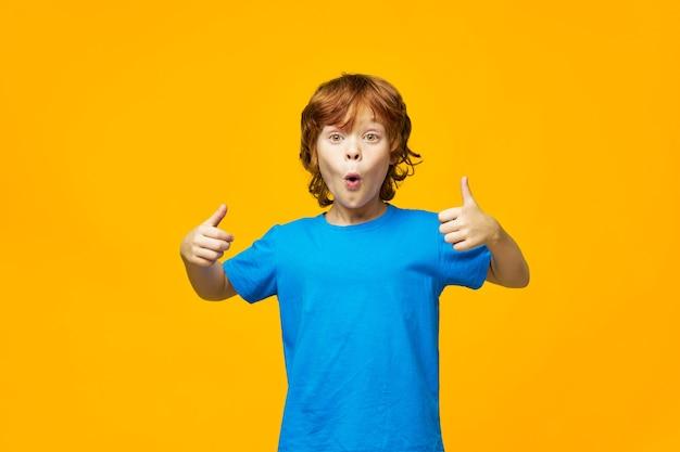 Zaskoczony rudowłosy dziecko gesty z rąk pozytywne gest emocji niebieski t-shirt studio