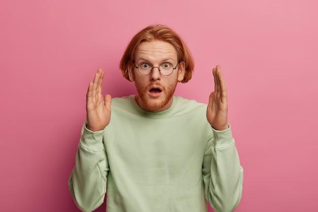Zaskoczony rudy mężczyzna ma otwarte usta, kształtuje bardzo duży przedmiot