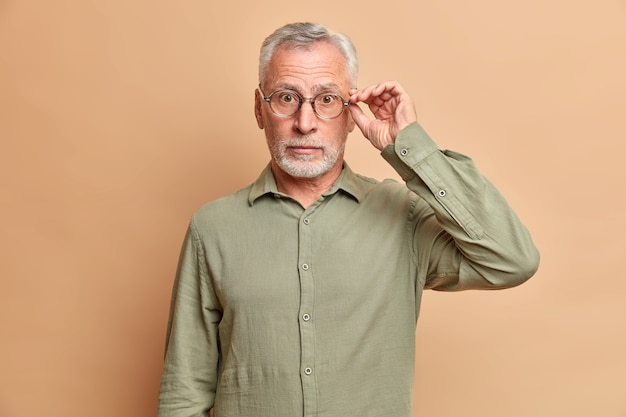 Zaskoczony, siwy, przystojny mężczyzna trzyma rękę na krawędzi okularów, słyszy niesamowite wieści, nosi formalną koszulę w pozach na brązowej ścianie