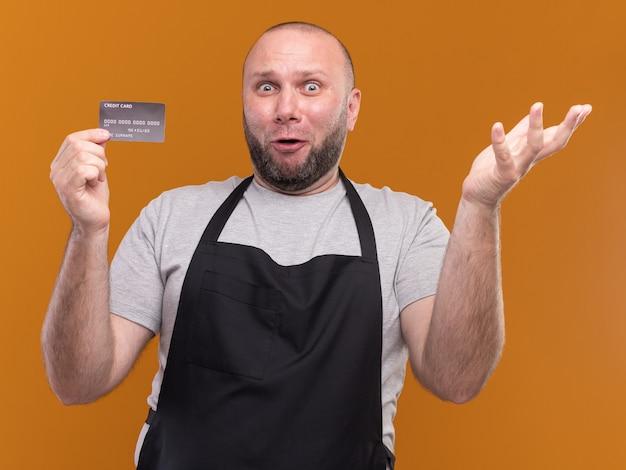 Zaskoczony słowiański mężczyzna w średnim wieku fryzjer w mundurze, trzymając kartę kredytową, rozkładając rękę na białym tle na pomarańczowej ścianie