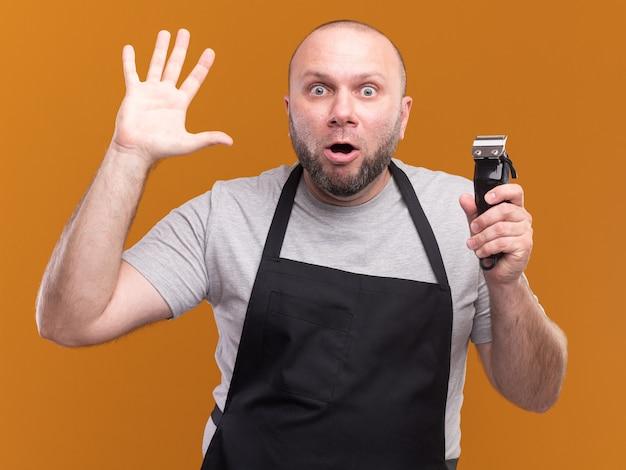 Zaskoczony słowiański mężczyzna w średnim wieku fryzjer w mundurze trzymając maszynkę do strzyżenia włosów pokazując pięć na białym tle na pomarańczowej ścianie
